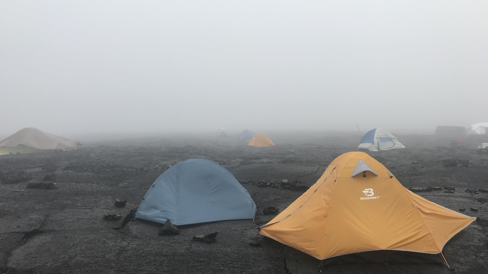 Des tentes sur un champ de roches, sous un brouillard épais