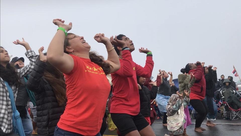 Des gens dansent sur une route, les bras levés vers le ciel