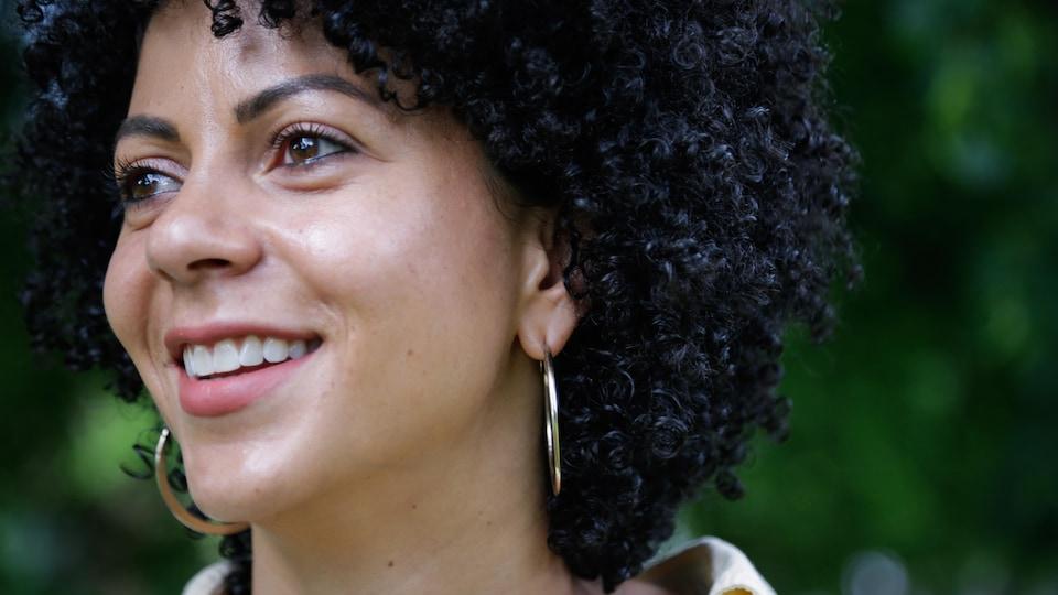 Photo d'une jeune femme qui sourit dans un parc.