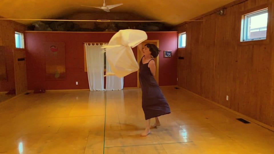 Heather Cameron danse dans une salle en agitant un long foulard.