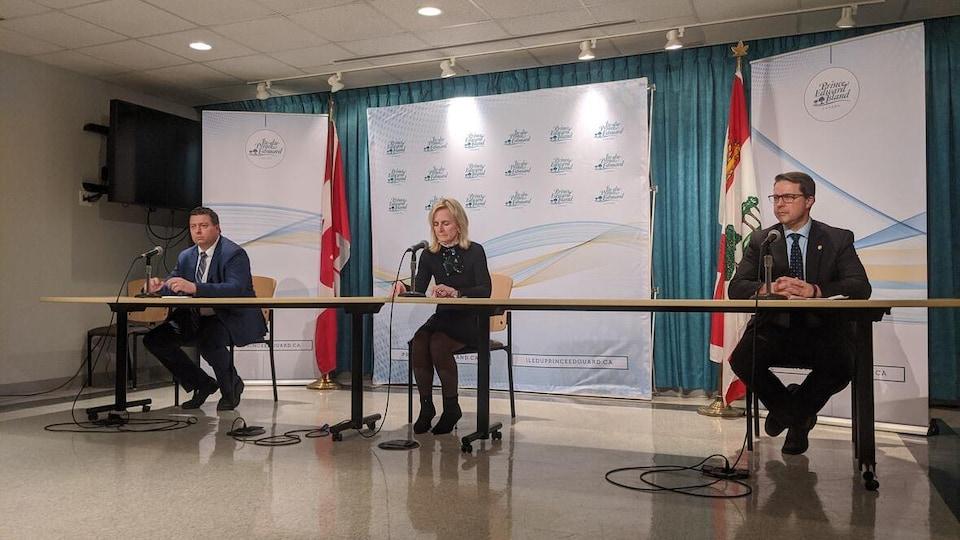 Trois personnes assises à deux mètres de distance les unes des autres pour une conférence de presse.