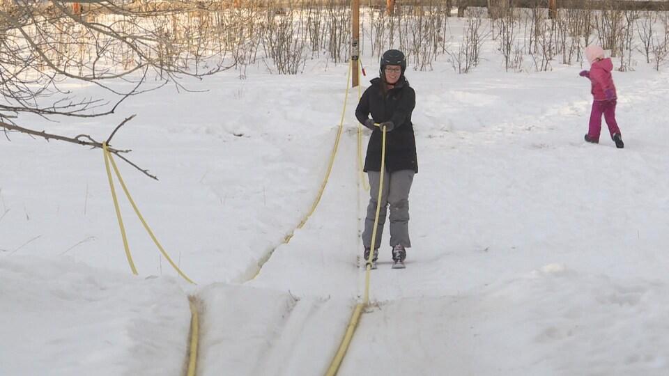 Une femme en ski remonte une pente en étant tirée par une corde.