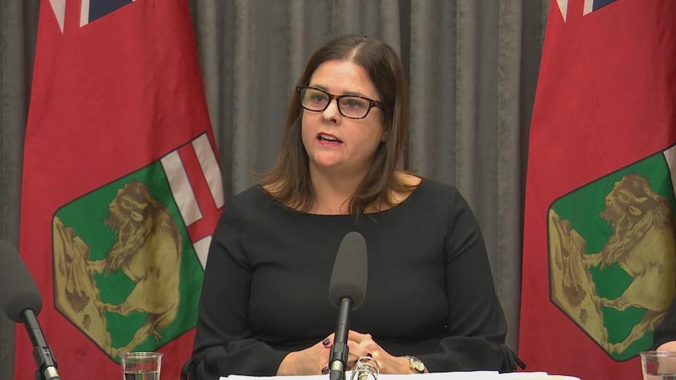La ministre des Familles, Heather Stefanson devant des drapeaux du Manitoba.