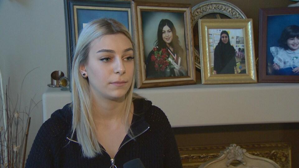 Heba Reslan a une expression sérieuse. Derrière elle, plusieurs photos de Nadia Atwi sont encadrées.