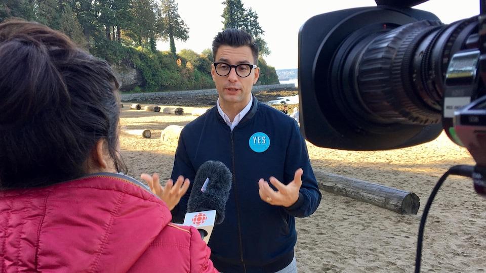 Hector Bremner répond aux questions de la journaliste sur le bord de la plage, on voit un bout de caméra dans la photo.