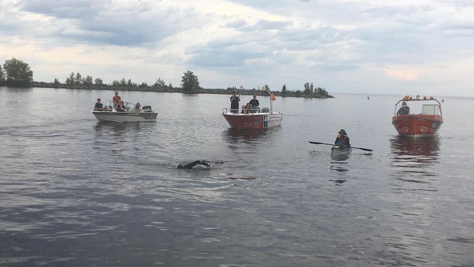 La nageuse, suivie de plusieurs embarcations, termine sa traversée sous un ciel gris.