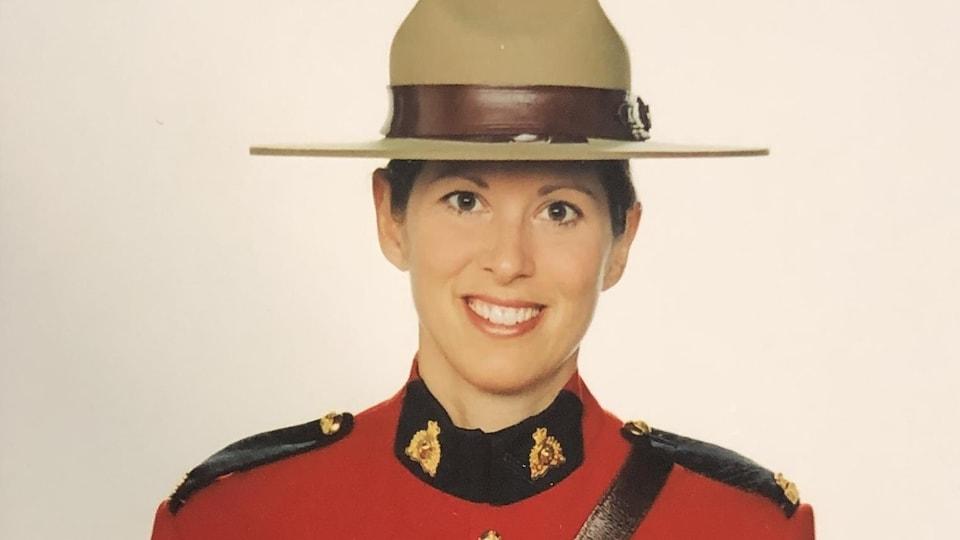 Portrait d'une policière en habit rouge et coiffée du chapeau traditionnel de la GRC.