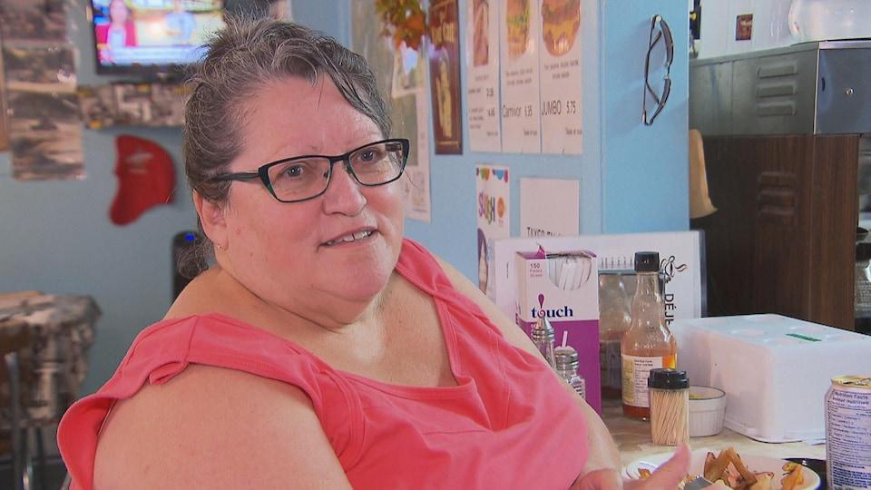 Une femme assise au comptoir d'un restaurant.