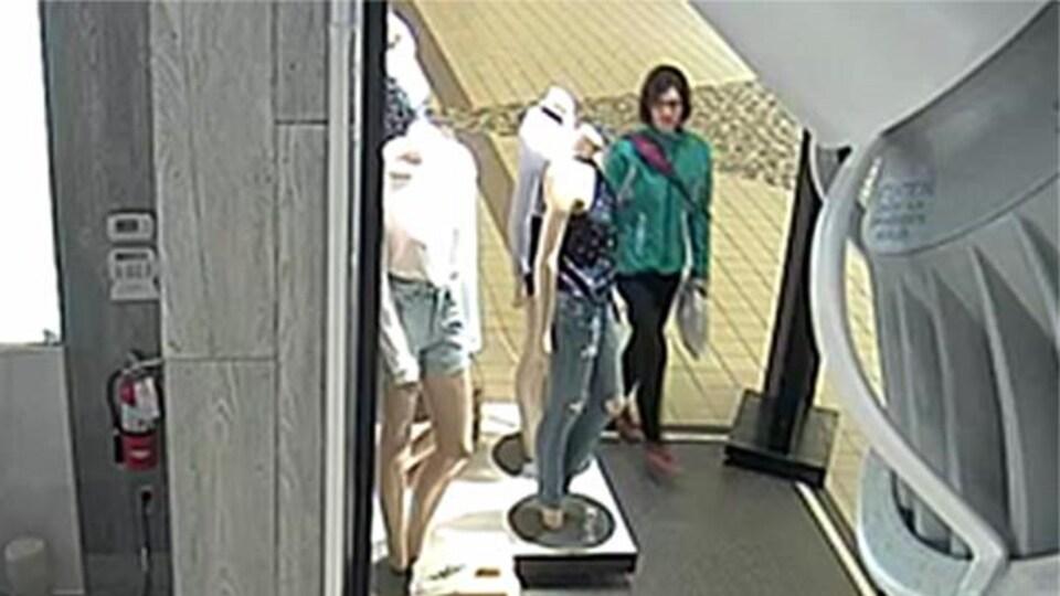 Image tirée d'une caméra de surveillance démontrant une femme qui entre dans une boutique.