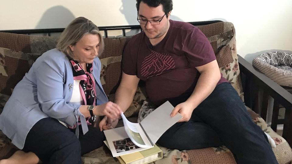 Hélène Napert et son fils Jean-François Cimon regardent un album des finissants de l'École régionale des Quatre-Saisons.