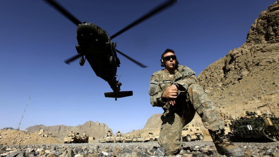 Un soldado se encuentra debajo de un helicóptero.