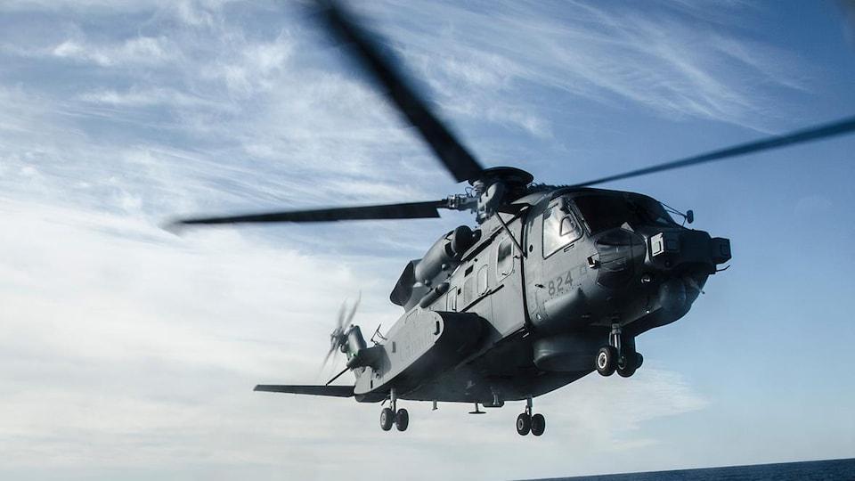 Un hélicoptère se pose sur un navire en mer.