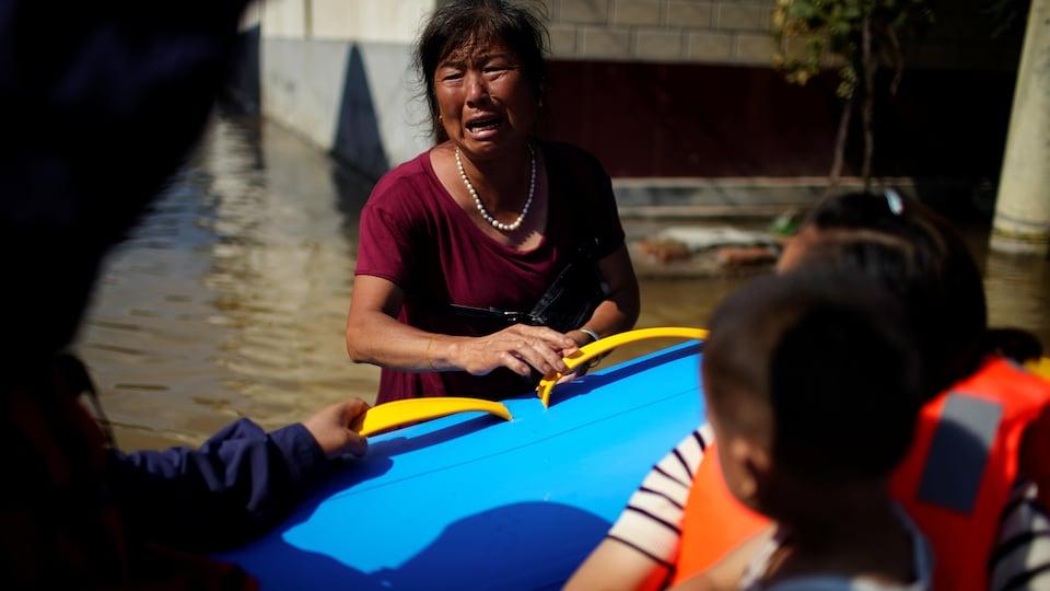 Une femme pleure près d'un bateau de sauvetage.