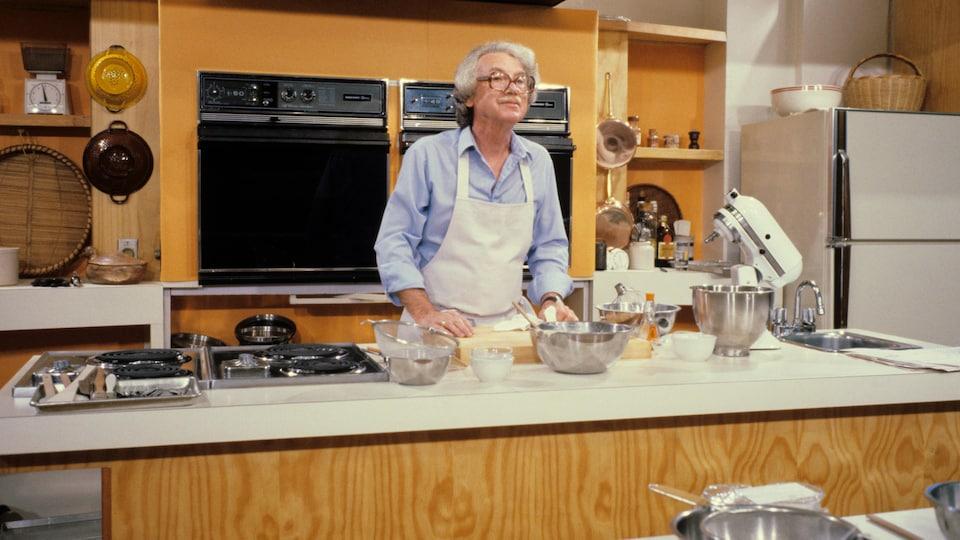 Dans une cuisine-laboratoire, Henri Bernard est debout derrière un plan de travail sur lequel il dépose ses mains.