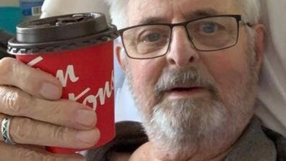 Un homme aux cheveux blancs dans un lit d'hôpital avec une tasse de café.