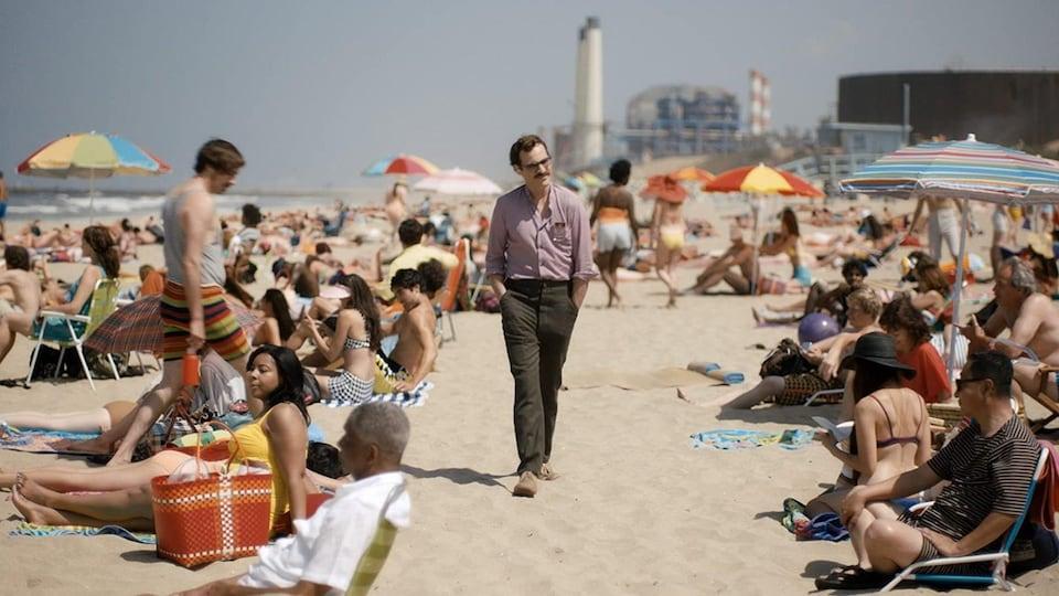 Un homme marche sur une plage.