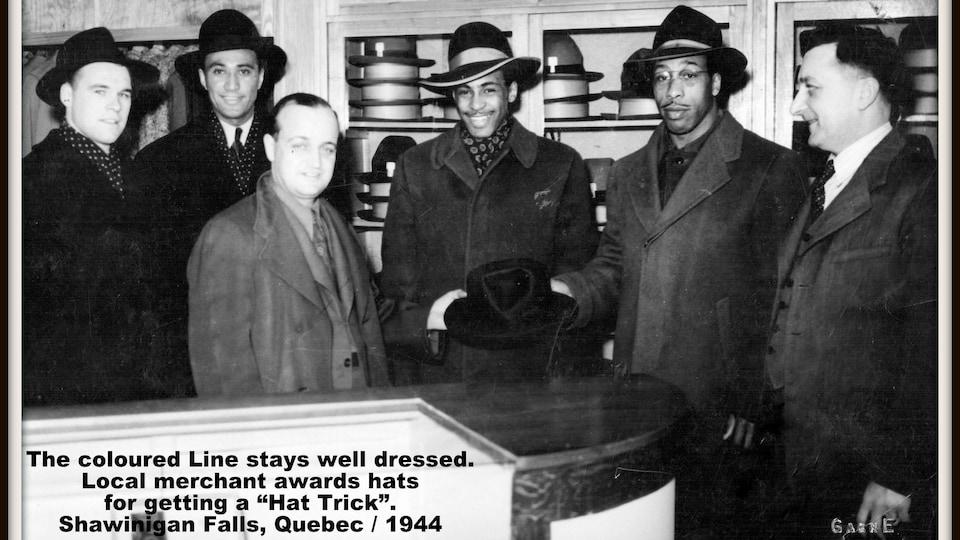 Plusieurs hommes tenant un chapeau posent pour une photo dans une boutique de couvre-chef.
