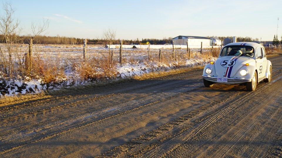 Une femme conduit une voiture sur une route de terre.