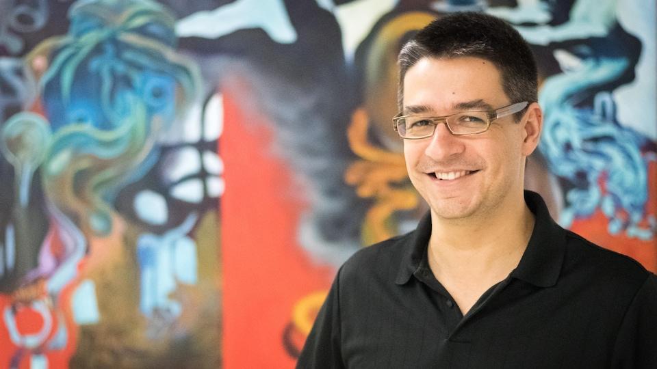 Une photo de Pierre-Alexandre Fournier, souriant, devant une toile très colorée.