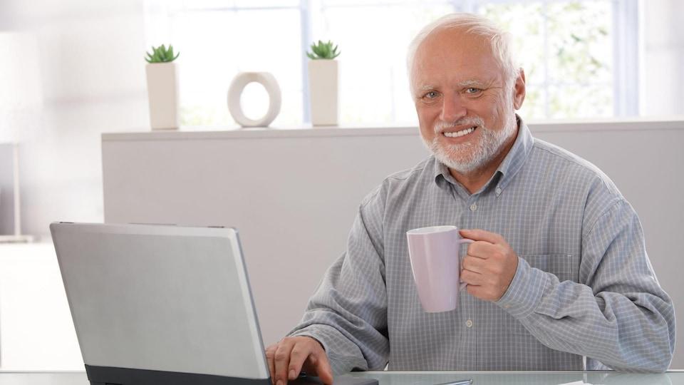 Un homme assis à un bureau tenant un café sourit.