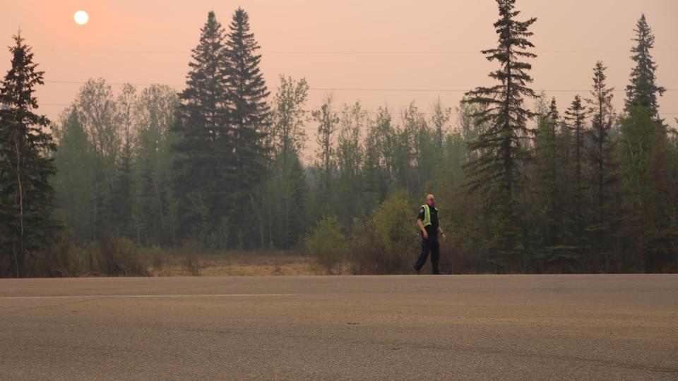 Un homme en uniforme portant un masque marche aux abords d'une forêt.