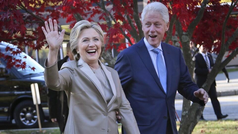 Hillary et Bill Clinton saluent le public à leur arrivée à un événement.