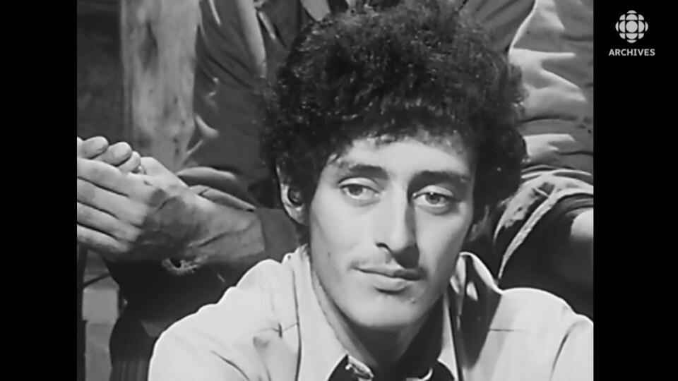 Gros plan sur le visage de Jean-Luc Arène dans une vidéo d'archives.