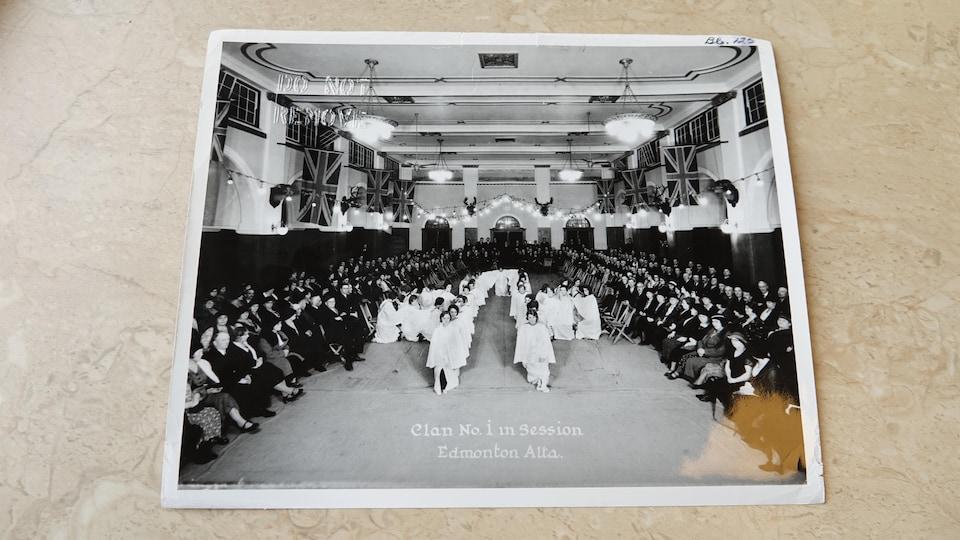Une photo en noir et blanc montrant des centaines de personnes assises le long des murs d'une grande salle au centre de laquelle sont assis des dizaines de personnes habillées d'une soutane blanche.