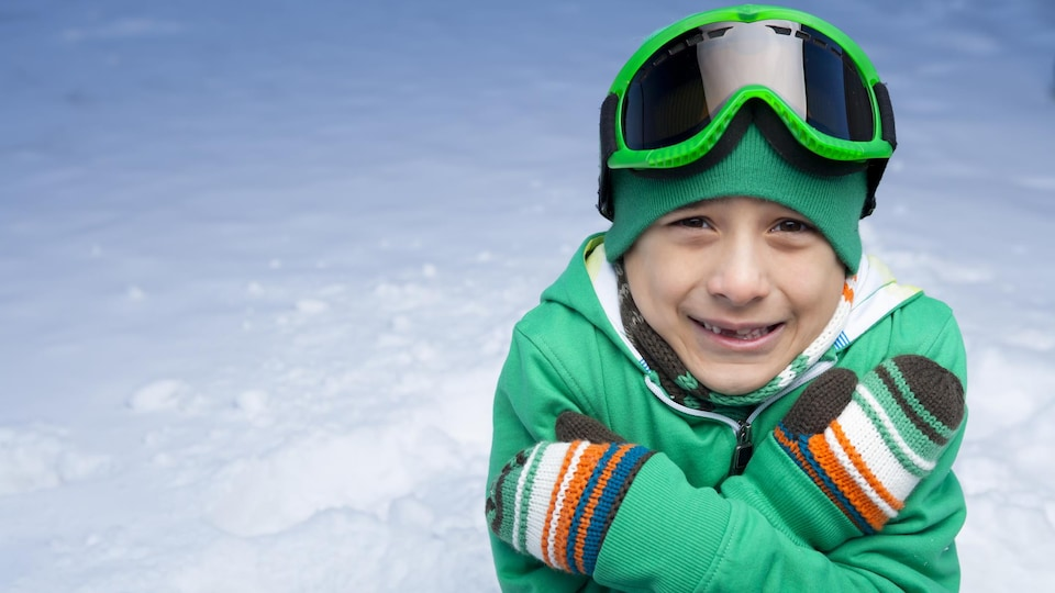 Un garçon de huit ans qui a froid et qui est triste.