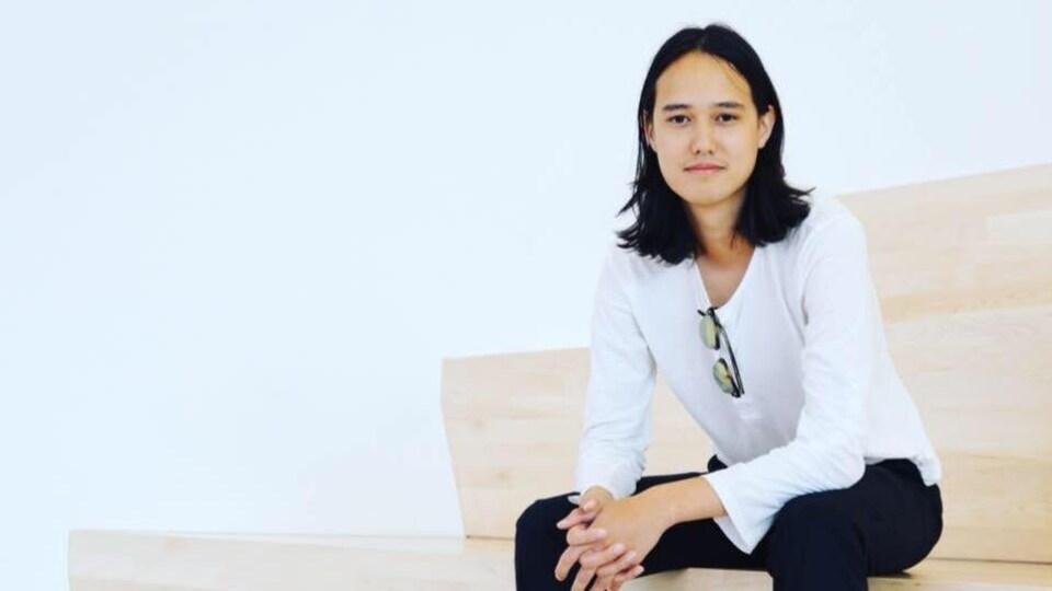 Hoan Ton-That assis sur des marches dans une photo studio.