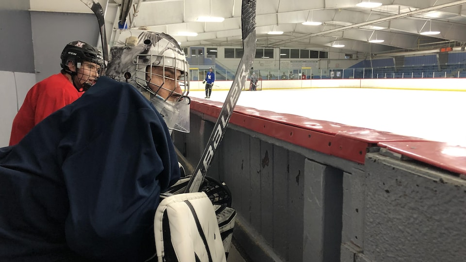 Un gardien de l'Académie Mount est assis sur le banc. Il regarde ses partenaires évoluer sur la glace.