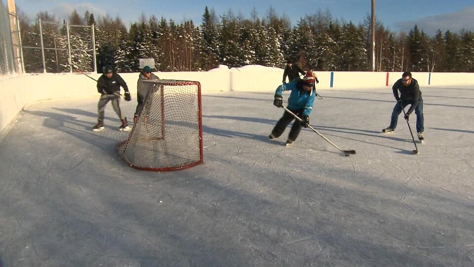 Les patineurs s'adonnent à du hockey de participation sur une patinoire extérieure de Sept-Îles