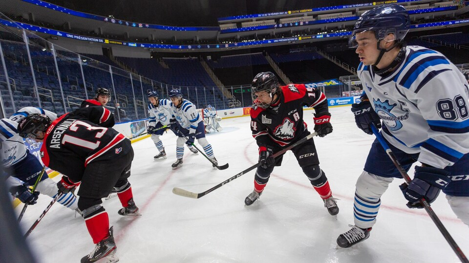 Des joueurs de hockey bataillent pour la rondelle dans une aréna vide.