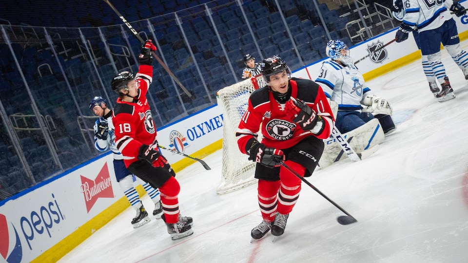 Des joueurs de hockey célèbrent un but.