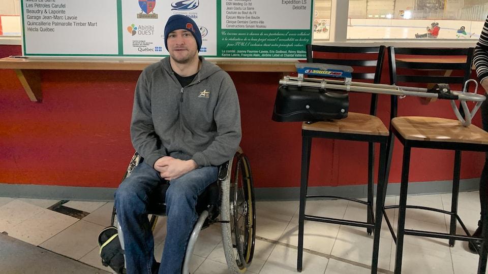 François Alain est assis dans un fauteuil roulant. Sur des chases à côté de lui est posé une luge à patins.