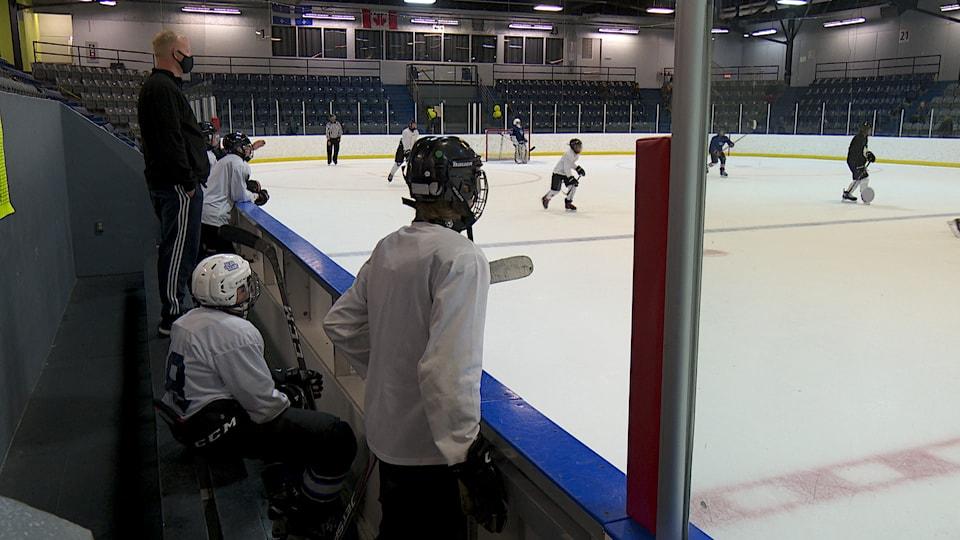 Sur le banc, des joueurs regardent leur coéquipiers sur la glace sous le regard de l'entraîneur qui porte un masque.