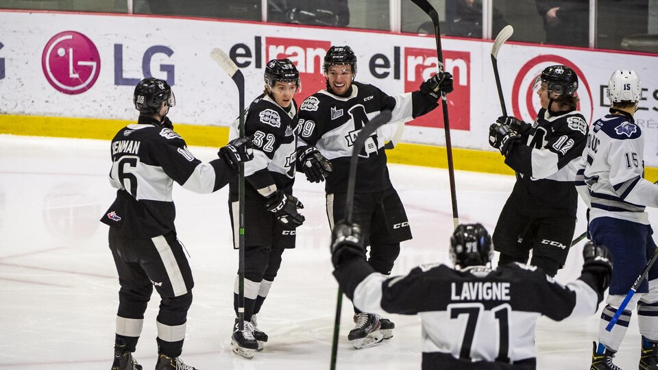 Des joueurs de l'Armada de Blainville-Boisbriand célèbrent sur la patinoire après un but.
