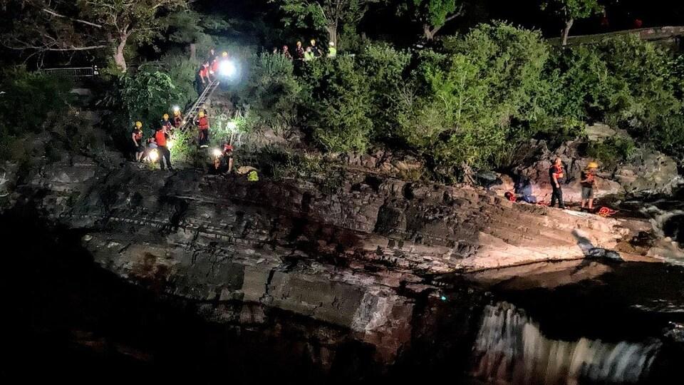 Des membres de l'équipe de sauvetage descendent une falaise la nuit.