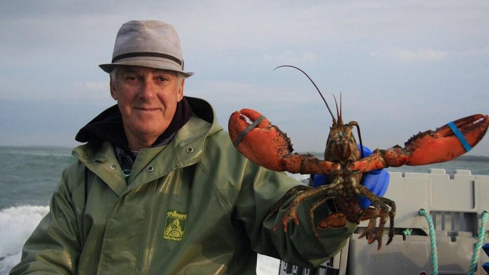 On voit un homme qui tient un homard en gros plan, sur un bateau de pêche.