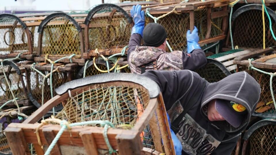 Des pêcheurs qui rangent des casiers à homard