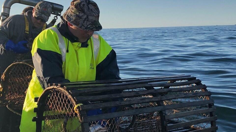 Deux pêcheurs sur leur bateau déposent des casiers à homard dans la mer.