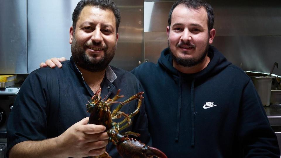 Le chef cuisinier tient un homard entre ses mains.
