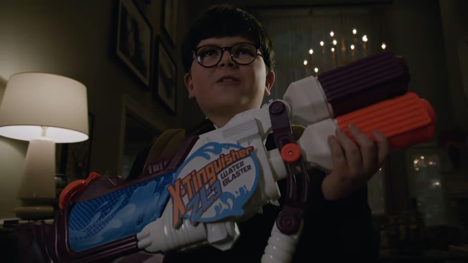 Le garçon tient un fusil à eau dans ses mains, à l'intérieur d'une maison.