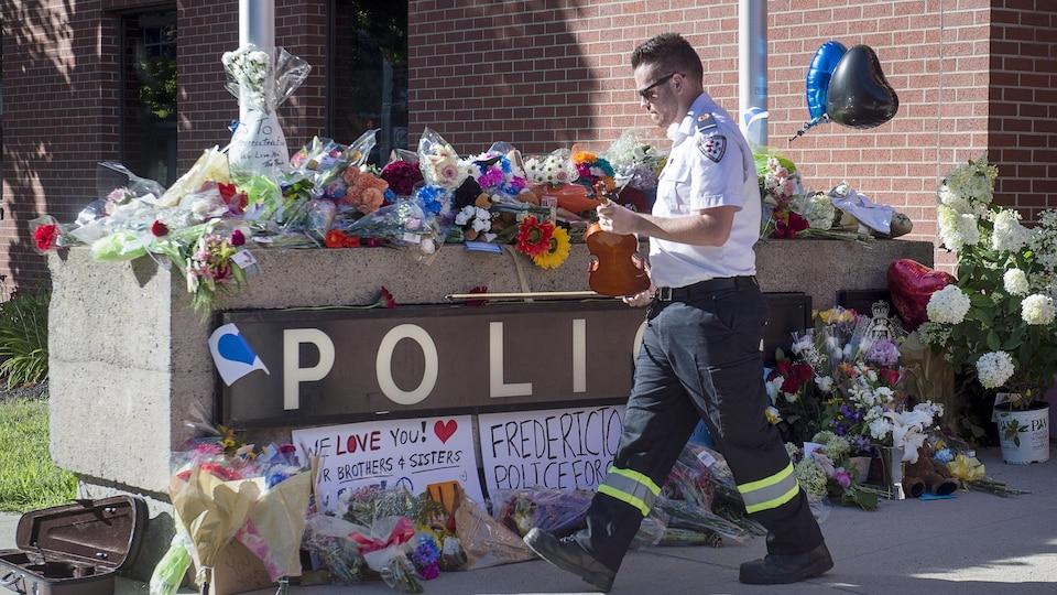 Un paramédic dépose le violon avec lequel il a joué un air en hommage aux policiers morts en service à Fredericton, dans un endroit où de nombreuses gerbes de fleurs ont été placées.