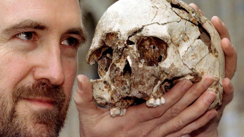 Un homme en gros plan tient un crâne à hauteur des yeux.