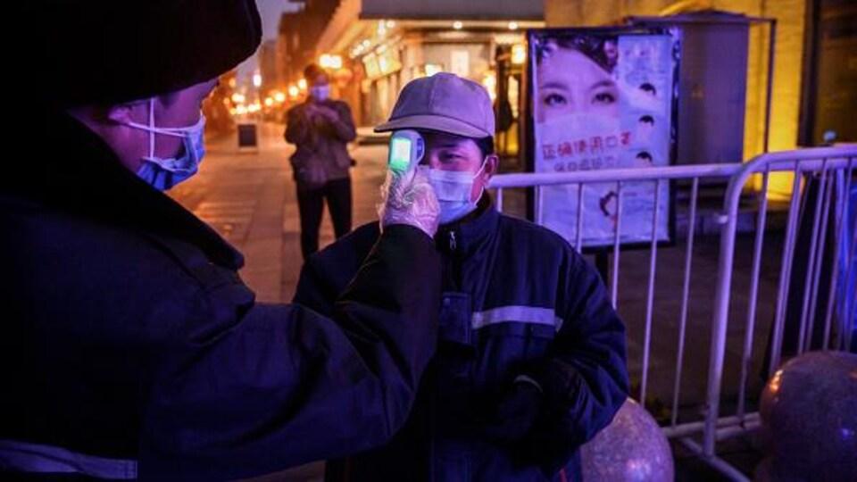 Un homme portant un masque de protection fait subir à une dame un contrôle de température.