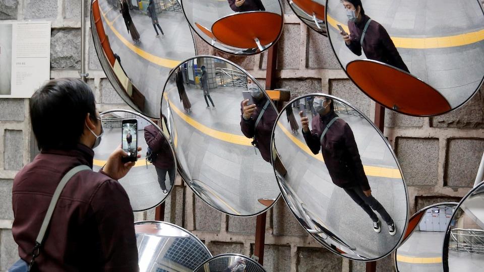Un homme qui porte un masque prend un égoportrait dans un miroir.