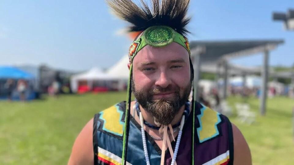 Un homme souriant, vêtu d'habits d'apparat traditionnels, dans un parc extérieur.