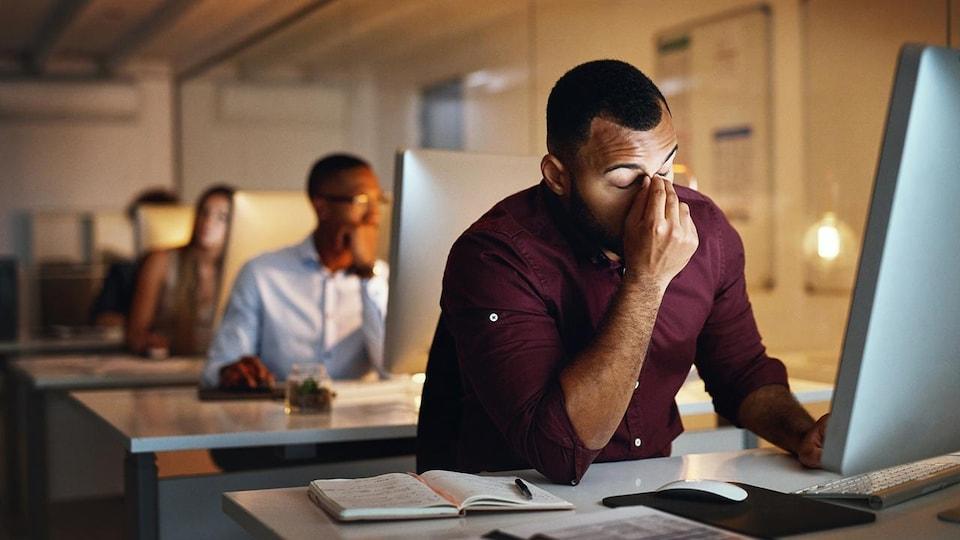 Un homme noir semble exaspéré devant son ordinateur