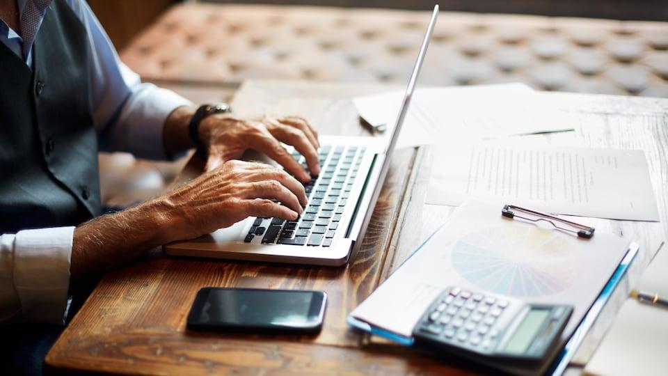 Installé à une table, un homme plus vieux, dont on ne voit pas la tête, utilise son ordinateur portable, devant lequel sont étalés des feuilles, une calculatrice et un téléphone intelligent.